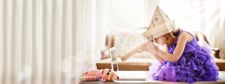Mädchen mit lila Kleid sitzt auf dem Tisch und spielt mit alten Zeitungen