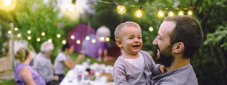 Vater mit kleinem Kind auf dem Arm freut sich bei einer Familienfeier im Garten über den günstigen Strompreis