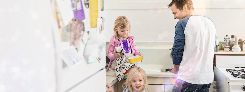 Vater bereitet zusammen mit seinen beiden Töchtern am Gasherd das Essen vor