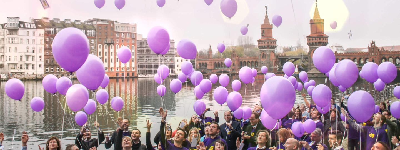 lekker Mitarbeiter lassen am Spreeufer lila Luftballons steigen.