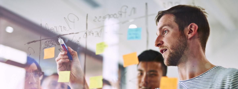 Mitarbeiter schreiben mit Marker auf ein Glasboard